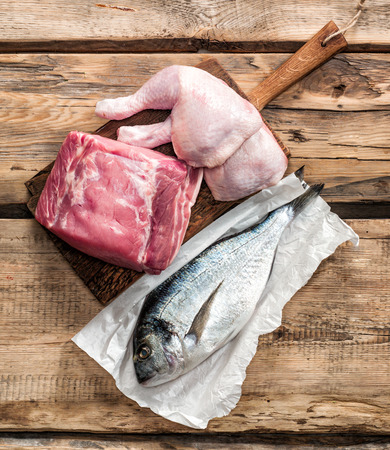 fish dinner: fresh raw meat products on wooden table Stock Photo