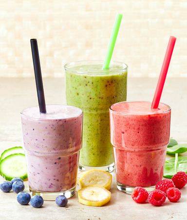 glasses of various smoothies with straws for healthy dieting breakfast