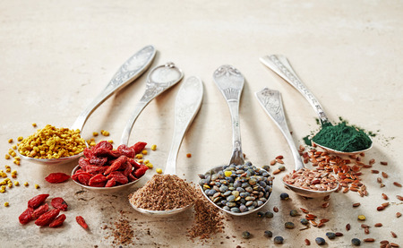 various kinds of healthy superfood seeds in silver spoons, top view