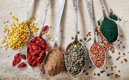 superfood: various kinds of healthy superfood seeds in silver spoons, top view