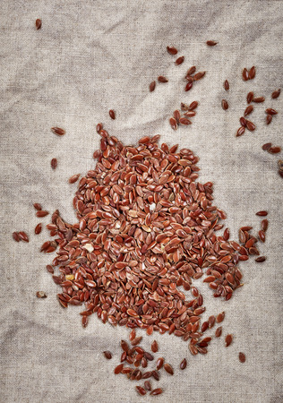 flax seeds: natural flax seeds on linen napkin, top view