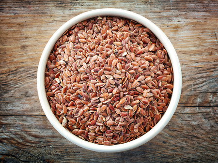 flax seeds: Bowl of flax seeds on old wooden table, top view