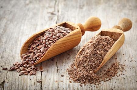 enteros y semillas de lino trituradas en tabla de madera Foto de archivo