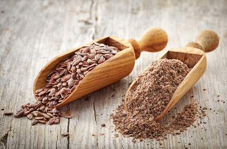 flax seeds: whole and crushed flax seeds on old wooden table