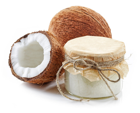 body oil: coconut oil and fresh coconuts isolated on white