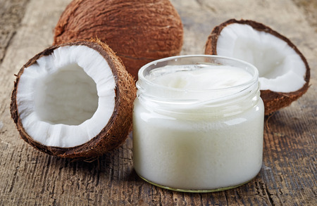 organic spa: coconut oil and fresh coconuts on old wooden table Stock Photo