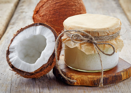aromatherapy oils: jar of coconut oil and fresh coconuts on wooden table