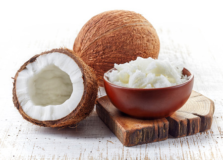 oil massage: bowl of coconut oil and fresh coconuts on white wooden table