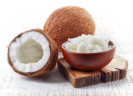 kom van kokosolie en verse kokosnoten op witte houten tafel