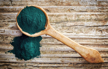 spoon of spirulina algae powder on wooden background, top view