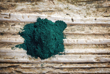 algae: heap of spirulina algae powder on wooden background, top view Stock Photo