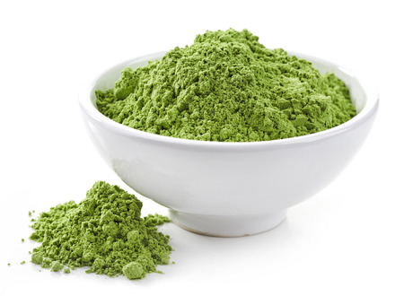 super macro: bowl of healthy wheat sprouts powder isolated on white Stock Photo