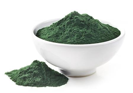 super macro: bowl of spirulina algae powder isolated on white