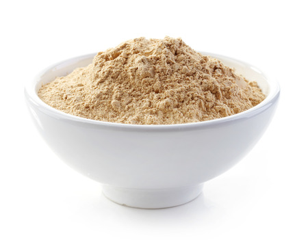bowl of maca powder isolated on white
