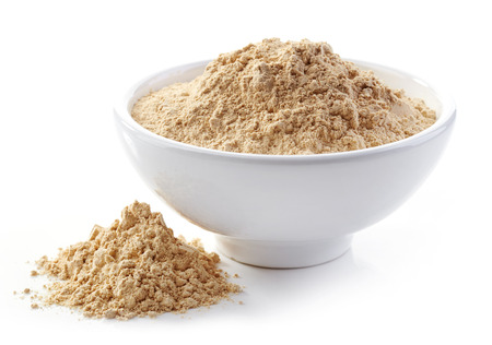 dry powder: bowl of maca powder isolated on white