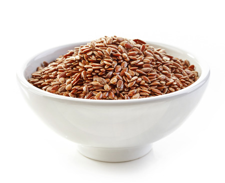 common flax: bowl of flax seeds isolated on white Stock Photo