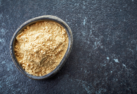 dry powder: bowl of healthy maca powder on dark background Stock Photo