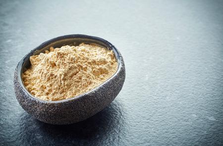 maca: taz�n de polvo de maca saludable sobre fondo oscuro
