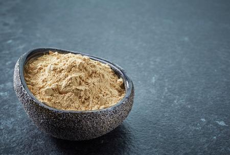 maca: bowl of healthy maca powder on dark background Stock Photo