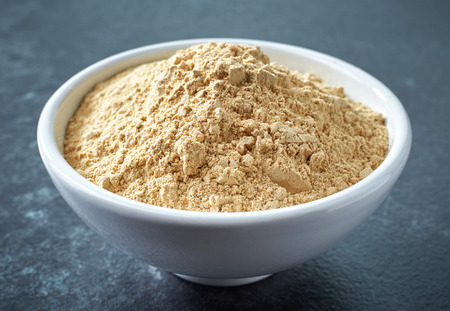 maca root: bowl of healthy maca powder on dark background Stock Photo
