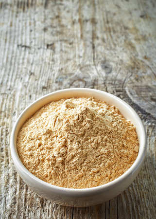 bowl of healthy maca powder on wooden table Banco de Imagens