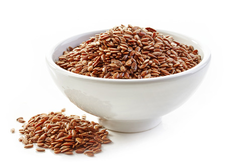 common flax: bowl of flax seeds isolated on white background