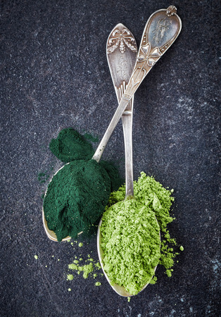 two silver spoons of spirulina algae and wheat sprouts powder