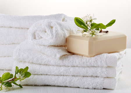 stack of white spa towels and soap bar
