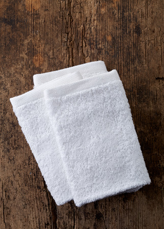 to white: white towels on wooden table, top view Stock Photo