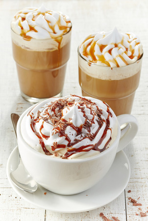 kinds: various kinds of coffee with whipped cream on white wooden table Stock Photo