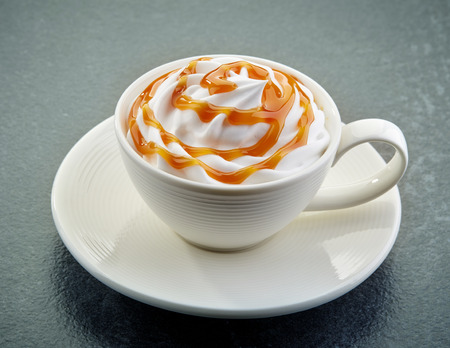 caramel: cup of caramel latte coffee with whipped cream on dark background Stock Photo