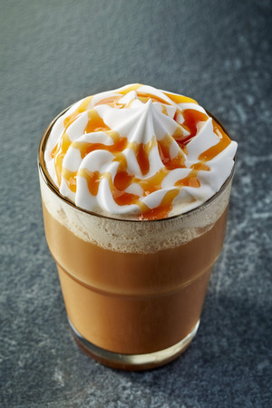 glass of caramel latte with whipped cream on dark table