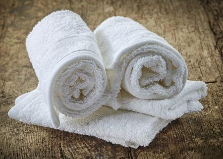 limpieza: blancas toallas de spa en la mesa de madera