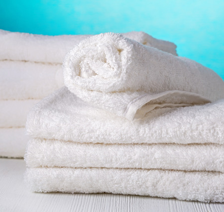 to white: stack of white spa towels on blue background