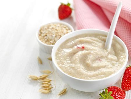 baby with spoon: bowl of baby food, healthy breakfast porridge