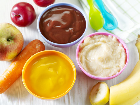 baby eating: various kinds of baby food in plastic bowls, top view