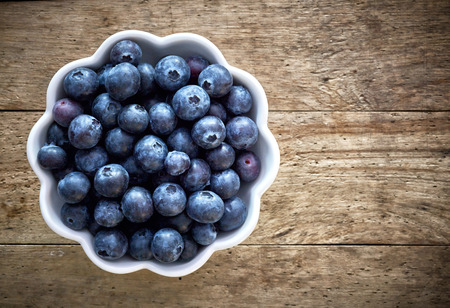 bowls: bowl of fresh organic blueberries on wooden table, top view
