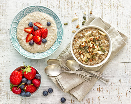 wooden spoon: two bowls of various porridge for healthy breakfast, top view Stock Photo