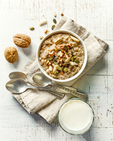 nuts: bowl of breakfast porridge with nuts and milk on white wooden table, top view