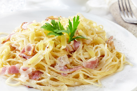 close up of pasta carbonara on white plate