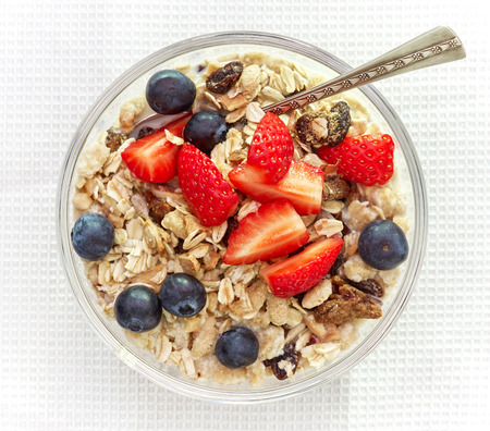 oats: healthy breakfast, bowl of muesli with milk and fresh berries