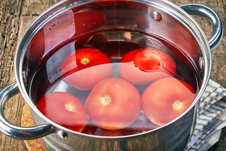 tomates: tomates maduros en una olla de agua Foto de archivo