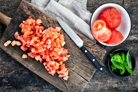 chopped tomatoes on wooden cutting board Stock Photo