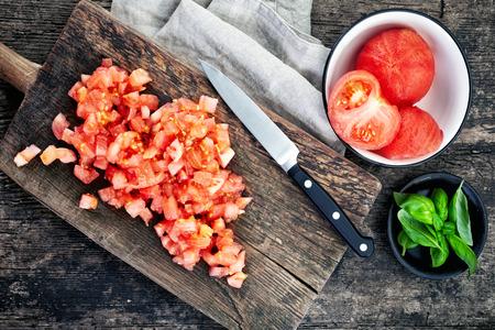ensalada tomate: los tomates picados en la tabla de cortar de madera