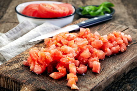 knife tomato: chopped tomatoes on wooden cutting board Stock Photo