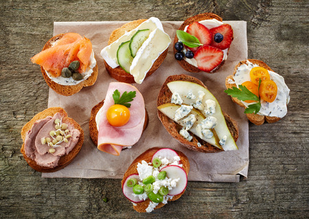 slices of bread: collection of toasted bread slices with various cheese and meats, top view Stock Photo