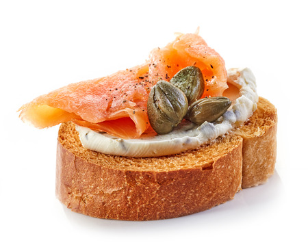 salmon ahumado: pan tostado con queso crema y salmón ahumado aislado en el fondo blanco