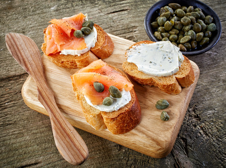 cutting board: toasted bread slices with cream cheese and smoked salmon on wooden cutting board Stock Photo