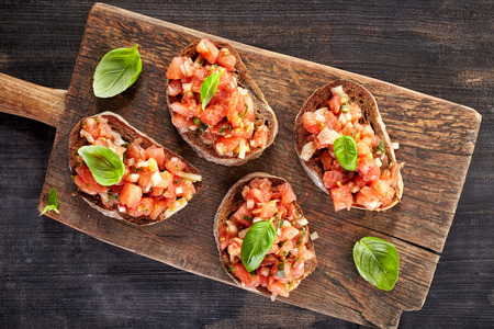toasted bread with chopped tomatoes on wooden cutting board, top view Stockfoto