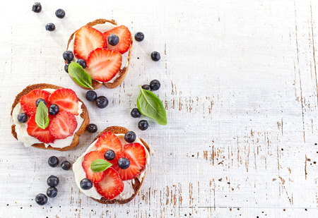toasted bread with cream cheese and strawberries on white wooden table